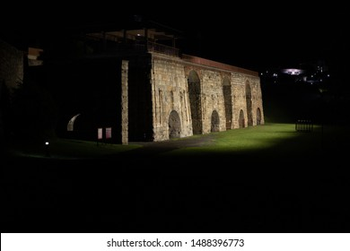 Scranton, PA, USA, August 24, 2019: Illustrative editorial image of the Scranton Iron Furnaces at night, with the University of Scranton lit up in the background.