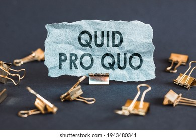 A scrap of blue paper with clips on a gray background with the text Quid Pro Quo.