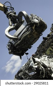 A scrap car being lifted by grab crane on to a pile of other scrapped cars.