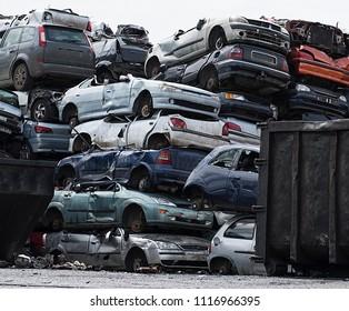 Scrap cars piled high in a scrapyard