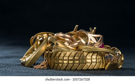 A scrap of gold. Old and broken jewellery, watches of gold and gold-plated on a dark background.