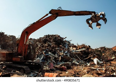 Scrap Metal Excavator Machine with Grapple Attachment Moving Scrap Iron and Steel Around Recycling Depot
