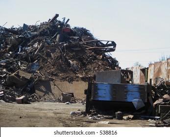 scrap metal yard with huge piles of rusty, gnarled metal
