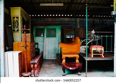 Scrap of old doors and damaged house windows at the repair workplace. Second-hand goods store. Used house parts for sale. Used vintage shop on the roadside