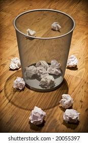 Scrap paper on wooden floor around waste paper basket
