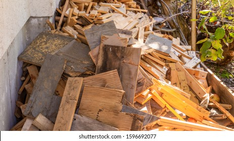 Scrap wood and lumber cuttings for firewood or junk removal service, in a pile. Useful for recycling projects or firewood, as reclaimed wood furniture or DIY decor, for a rustic, weathered wood look.
