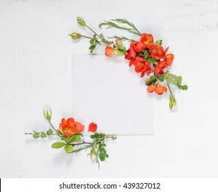Scrapbook page of wedding or family photo album, frame with red  Chaenomeles japonica flowers and green leaves on light wooden background; top view, flat lay, overhead view