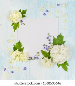 Scrapbooking page of wedding or family photo album, frame with fresh white and blue flowers and green leaves and flower petals on light wooden background; top view, flat lay, overhead view