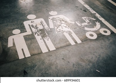 Scraped or Damaged Car Parking Sign Reserved for family with children on empty parking lot, symbolic conceptualized for broken or crumbled or split or divorced and fallen apart family