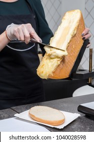 Scraping melted traditional Swiss Raclette cheese