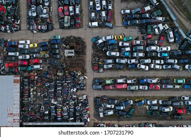Scrapyard or junkyard with broken cars and car parts from above. The scrap yard was captured by a drone. Frankfurt, Hessen/Germany - 25.01.20.