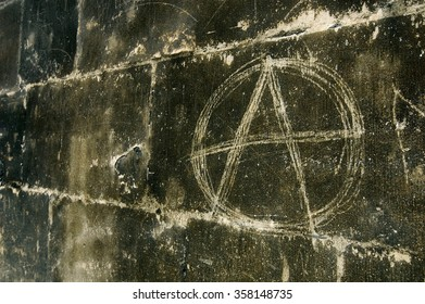 Scratched anarchy symbol on house wall