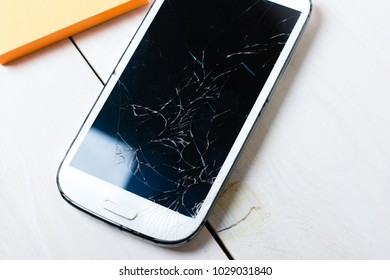 Scratched and broken smartphone on white wooden table background. Closeup. Selective focus. Big scratches. Black mirror.