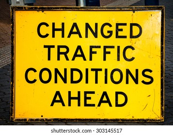 Scratched and damaged yellow and black temporary street sign warning CHANGED TRAFFIC CONDITIONS AHEAD