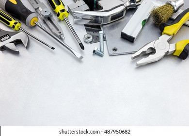 scratched metal background with yellow tool set and instruments for hand work and fixing