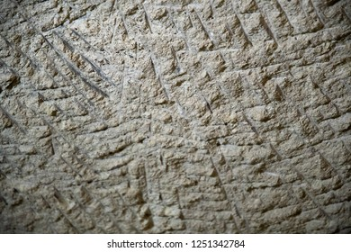 Scratched surface of limestone wall in cave of Cappadocia Turkey. Natural limestone textured background. Grunge backdrop in shades of grey. Ancient wall structure closeup. Rough stone texture.