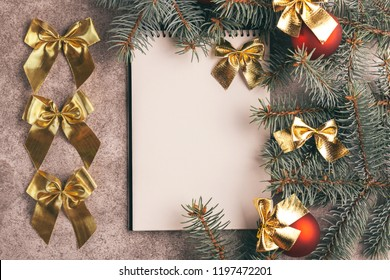 Scratchpad  for wishes with Christmas decorations - Christmas tree branches and balls on slate marble background. Top view. Copy space. Flat lay