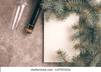Scratchpad  for wishes with Christmas decorations - Christmas tree branches and wineglass on slate marble background. Top view. Copy space. Flat lay