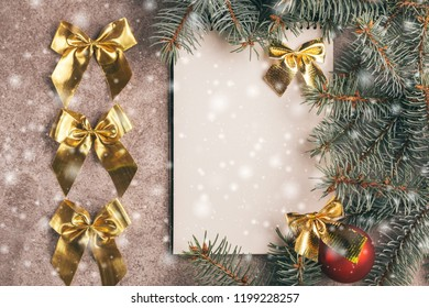 Scratchpad  for wishes with Christmas decorations - Christmas tree branches and ball on slate marble background. Top view. Copy space. Flat lay