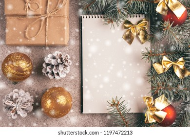 Scratchpad  for wishes with craft gift boxes and Christmas decorations - Christmas tree branches and cones on slate marble background with snow effect. Top view. Copy space. Flat lay