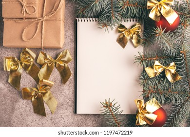 Scratchpad  for wishes with craft gift boxes and Christmas decorations - Christmas tree branches and cones on slate marble background. Top view. Copy space. Flat lay