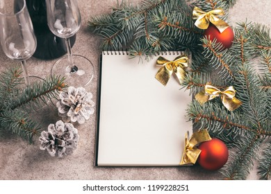 Scratchpad  for wishes with wineglasses and Christmas decorations - Christmas tree branches and cones on slate marble background. Horizontal view. Copy space.