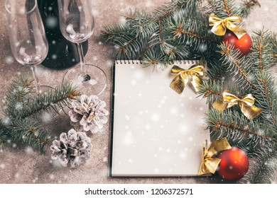 Scratchpad  for wishes with wineglasses and Christmas decorations - Christmas tree branches and cones on slate marble background with snow effect. Horizontal view. Copy space.