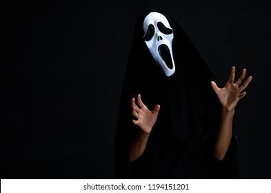Scream devil costume, someone in black cover put on white ghost mask on face. Devil cosplay and acting in clamber manner on black background, concept for funny dress halloween festival or carnival.