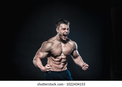 Scream of rage in the bodybuilder during training. Bodybuilding, fitness model. Emotions.