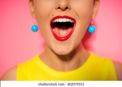 Scream and shout! Close up of opened female mouth. Bright red lips. Pink background
