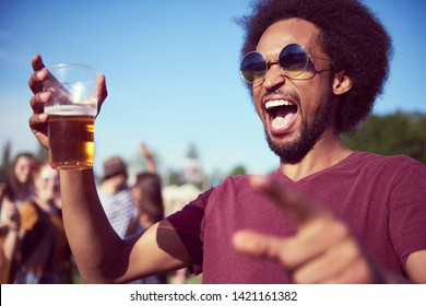 Screaming African man drinking beer at the music festival