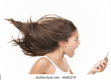 Screaming angry woman on the mobile phone. Dynamic and energetic image of young mixed race chinese / caucasian woman isolated on seamless white background.