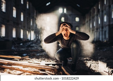 Screaming anxious person in abandoned destroyed building crying.Emotional portrait.Mentally ill woman with bipolar disorder and psychosis.Schizophrenia.Madness, crazy person.Voices in head.Tinnitus