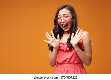 Screaming asian woman in pink glasses on empty orange background