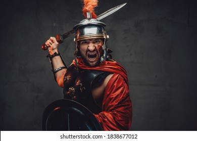 Screaming and assaulting mad roman warrior in armour and red mantle holding sword and shield in dark background.