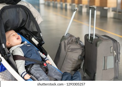 Screaming baby boy sitting in stroller near luggage at airport terminal. Child in carriage near check-in desk counter. Children tears, panic and hysterics. Travelling with small children concept.