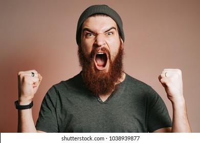 Schreie bärtige brutale Mann und Blick auf die Kamera mit den Händen nach oben, Goal, Gewinner, Feiern. Gesichtsausdruck. Verrückter Mann mit Bart.