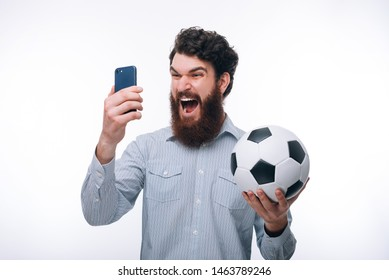 Screaming bearded man in casual looking at smartphone and holding soccerball