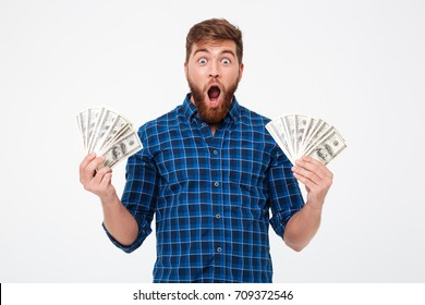 Screaming bearded man in checkered shirt holding money in hands and looking at the camera over gray background