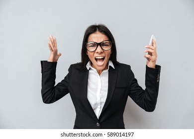 Screaming Business woman in suit and eyeglasses which holding phone in hand and looking at camera. Isolated gray background