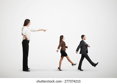 screaming businesswoman in formal wear commanding her subordinates over light grey background