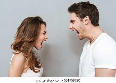 Screaming couple looking at each other. Isolated gray background