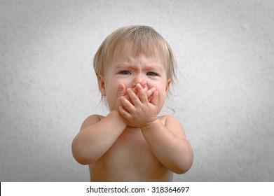 Screaming crying baby covering mouth by hand, frightened child face, very emotional sad little girl, unhappy kid in hysterical scream feeling fear