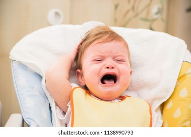 Screaming crying little baby sitting in a highchair. Dealing with children's hysterics concept