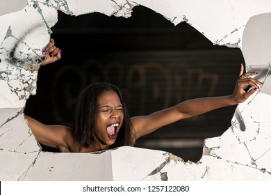 Screaming ethnic woman breaking through wall standing in hole with eyes closed