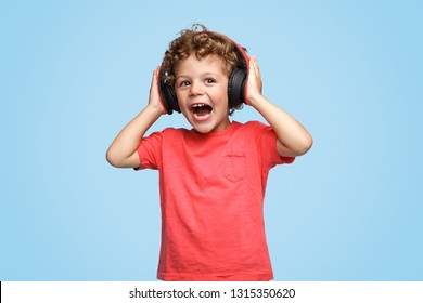 Screaming excited curly kid in headphones listening to music on blue background