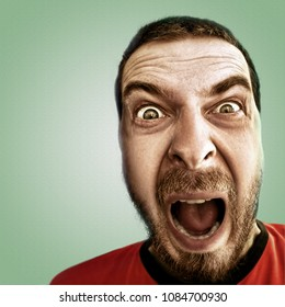 Screaming face of shocked funny man isolated on green
