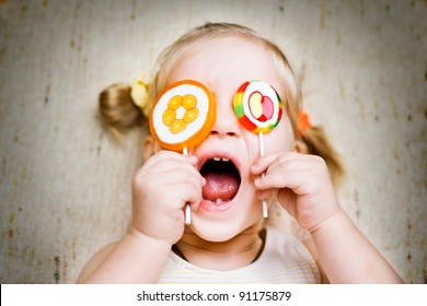 Screaming happy girl with eyes covered by candies