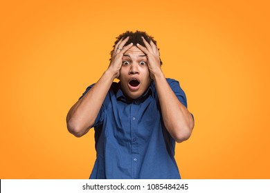 Screaming, hate, rage. Crying emotional angry man screaming on orange studio background. Emotional, young face. male half-length portrait. Human emotions, facial expression concept. Trendy colors
