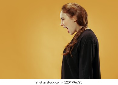 Screaming, hate, rage. Crying emotional angry woman screaming on gold studio background. Emotional, young face. Female half-length portrait. Human emotions, facial expression concept. Trendy colors